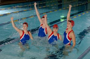 Swim team celebrating in swimming poolの写真素材 [FYI01985582]