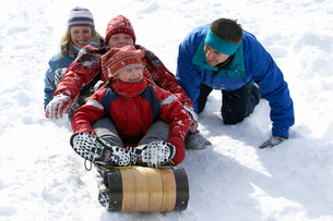 Family sledding down snowy hillの写真素材 [FYI01985649]