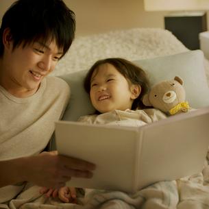 ベッドで絵本の読み聞かせをする親子の写真素材 [FYI01985667]