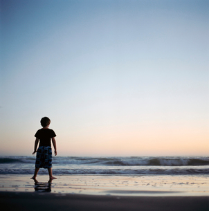 Young boy standing by wavesの写真素材 [FYI01985673]