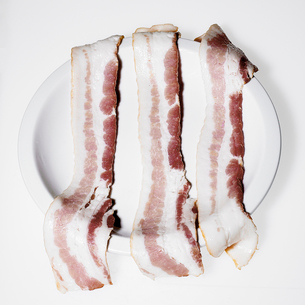 Raw bacon on a plateの写真素材 [FYI01985680]