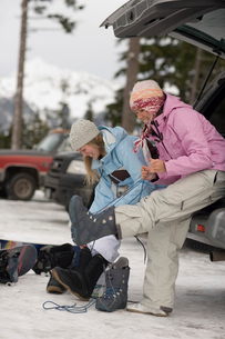 Young women putting on snowboard bootsの写真素材 [FYI01985756]