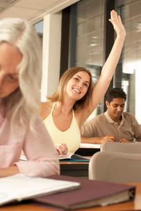 Female student raising her hand in classの写真素材 [FYI01985789]