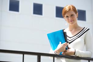Woman holding books on railingの写真素材 [FYI01985821]