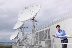 man standing on balcony with satellitesの写真素材 [FYI01985858]