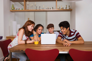 Four teenagers looking at laptop indoorsの写真素材 [FYI01985870]
