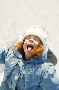 Young girl sticking tongue out in snowの写真素材 [FYI01985934]