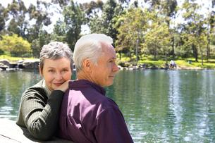 Senior couple sitting by pondの写真素材 [FYI01986007]