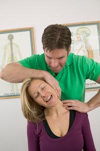 Doctor cracking womans neckの写真素材 [FYI01986028]