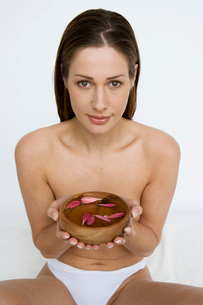 Woman holding a bowl of rose petalsの写真素材 [FYI01986087]