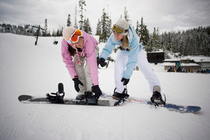 Women strapping boots to snowboardsの写真素材 [FYI01986091]