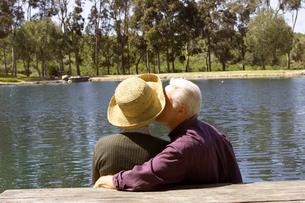 Senior couple kissing by pondの写真素材 [FYI01986138]
