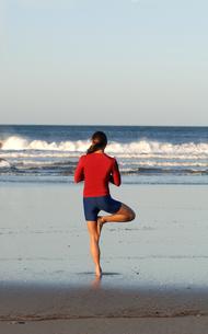 Asian woman in yoga pose on beachの写真素材 [FYI01986166]