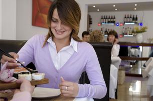 Woman eating sushi at restaurantの写真素材 [FYI01986199]
