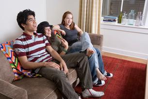 Three teenagers sitting on sofa laughingの写真素材 [FYI01986211]