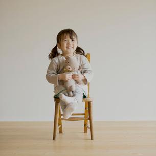 椅子に座りクマのぬいぐるみを持つ女の子の写真素材 [FYI01986249]
