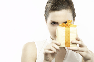 Woman holding wrapped present with bowの写真素材 [FYI01986290]