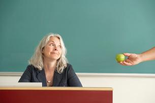 Teacher receiving an apple from studentの写真素材 [FYI01986302]