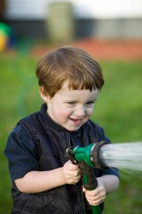 Young boy using garden hoseの写真素材 [FYI01986308]
