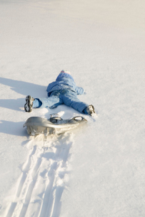 Child falling off sled in snowの写真素材 [FYI01986323]