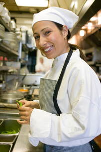 Hispanic female chef cooking in kitchenの写真素材 [FYI01986342]