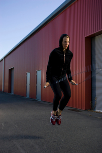 Woman jumping rope near warehouseの写真素材 [FYI01986349]