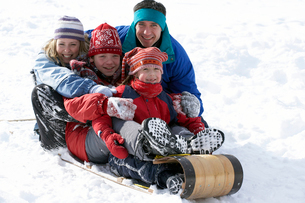 Family sledding down snowy hillの写真素材 [FYI01986356]