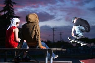 Teenagers watching friend do skateboardの写真素材 [FYI01986412]