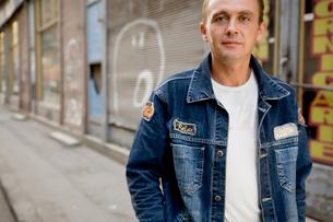 Man in jean jacket on urban streetの写真素材 [FYI01986422]