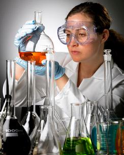 Woman in lab coat examining liquidの写真素材 [FYI01986519]