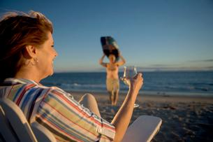 Mature woman watching husband on beachの写真素材 [FYI01986532]