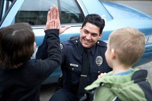 Male police officer high-fiving a Boyの写真素材 [FYI01986636]