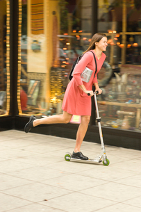Woman pushing scooter past storefrontの写真素材 [FYI01986691]