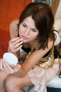 Woman checking makeup in hand mirrorの写真素材 [FYI01986747]