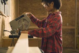 Teenage girl using circular sawの写真素材 [FYI01986756]