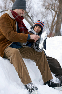 Father helping son put on ice skatesの写真素材 [FYI01986799]