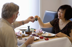 Adult couple eating sushi at restaurantの写真素材 [FYI01986825]