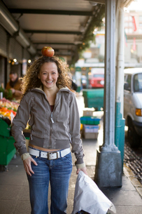 Woman balancing an apple on her headの写真素材 [FYI01986908]