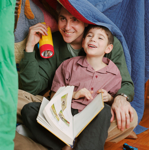 Father and son reading under blanketの写真素材 [FYI01986916]