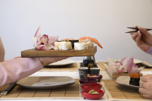 Woman's hand holding tray of sushiの写真素材 [FYI01987053]