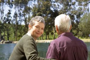 Senior couple sitting by pondの写真素材 [FYI01987056]
