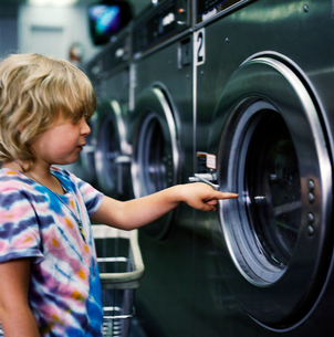 Young girl pointing at washing machineの写真素材 [FYI01987060]