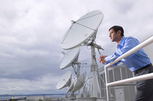 man standing on balcony with satellitesの写真素材 [FYI01987095]