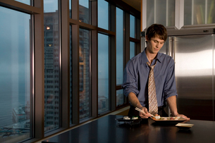Young adult man eating sushi in kitchenの写真素材 [FYI01987116]
