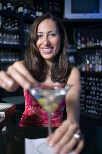 Hispanic woman making cocktail in barの写真素材 [FYI01987190]