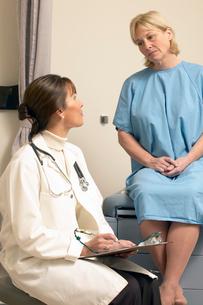 Forlorn woman talking to doctorの写真素材 [FYI01987203]