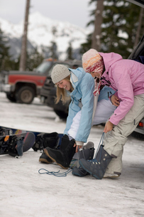 Young women putting on snowboard bootsの写真素材 [FYI01987286]