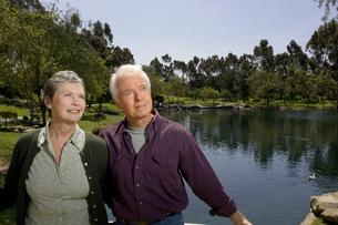 Senior couple standing by pondの写真素材 [FYI01987334]