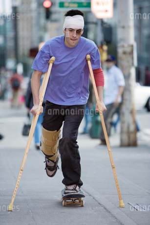 Man on crutches riding a skateboardの写真素材 [FYI01987377]