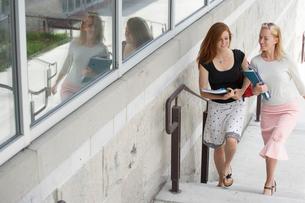 Women carrying books up stairsの写真素材 [FYI01987416]